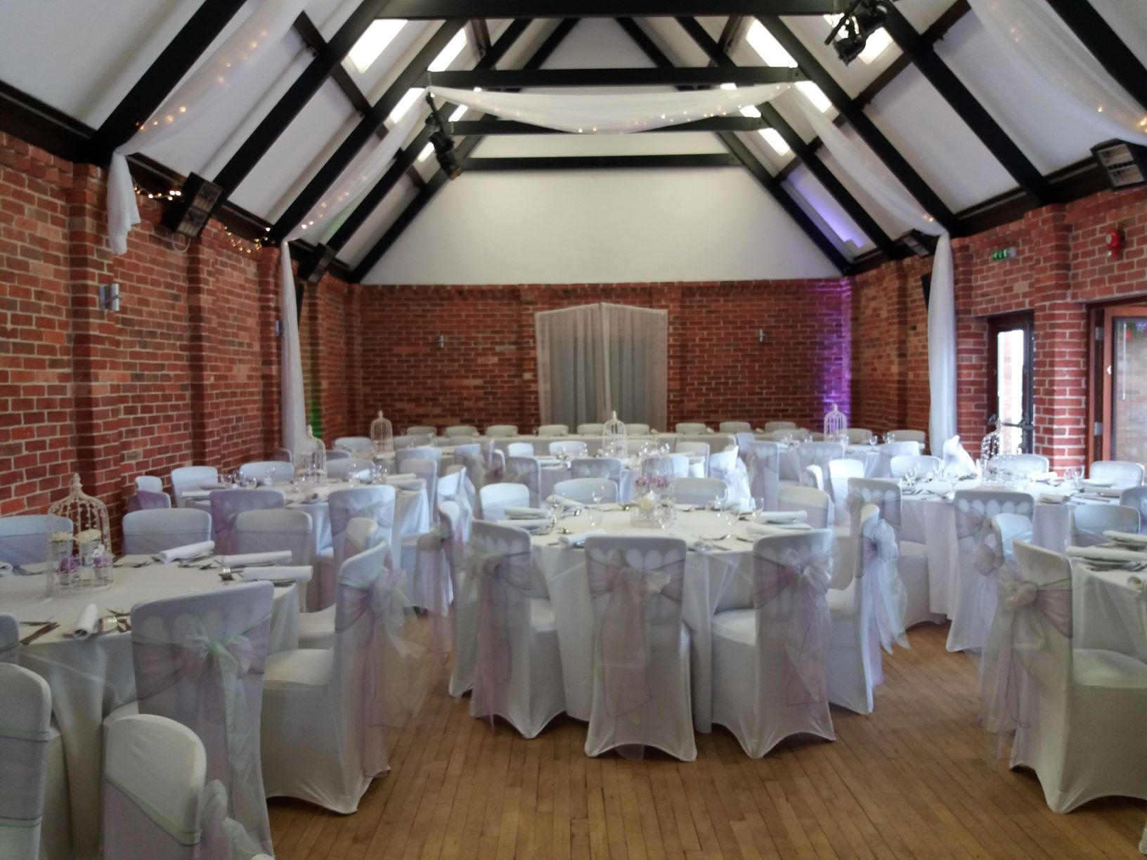 Ceiling drapes, chair covers and sashes by Add A Little Sparkle at Eversholt village Hall