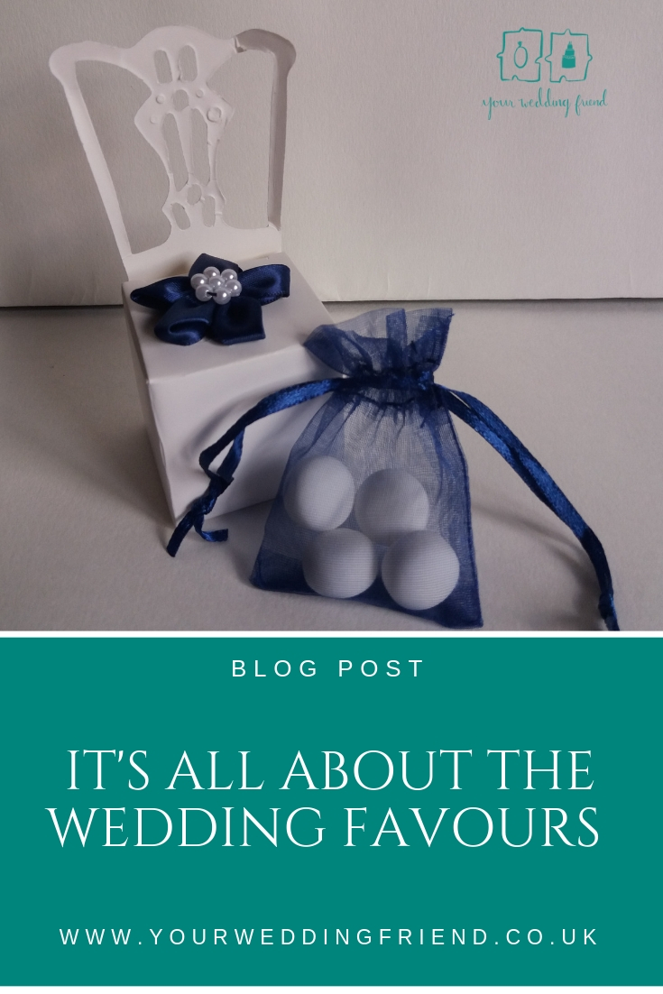 Image is of favour box in the shape of a chair with a navy blue bow on the seat and in front of it a navy blu echiffon bag with 4 mint imperials inside. The logo and blog title are also shown.
