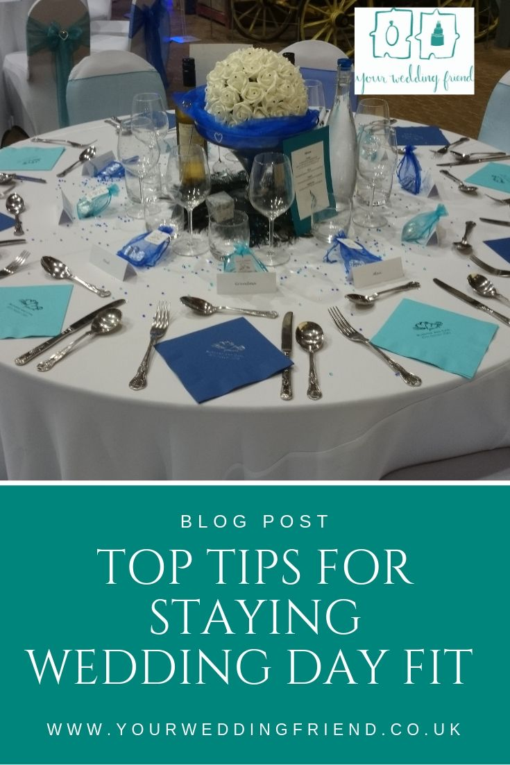 the picture is of a wedding breakfast table with royal and pale blue napkins and chairs with white covers and matching blue bows, the round table has a white cloth and in the centre is a flower display bottles of wine and water and glasses