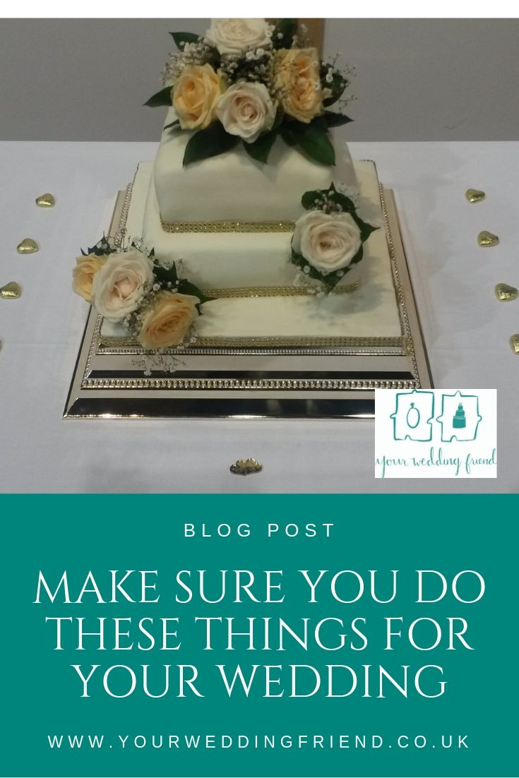 Picture is of a three tiered white wedding cake with ivory and rose gold roses on a white clothed table