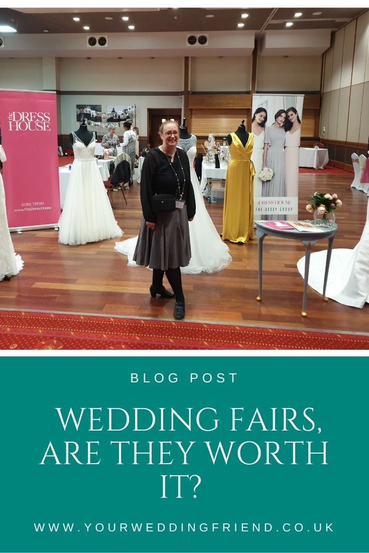 the image is of me at my DIY wedding fair in October 2019 surrounded by wedding dresses from The Dress House, bridalwear shop in Luton