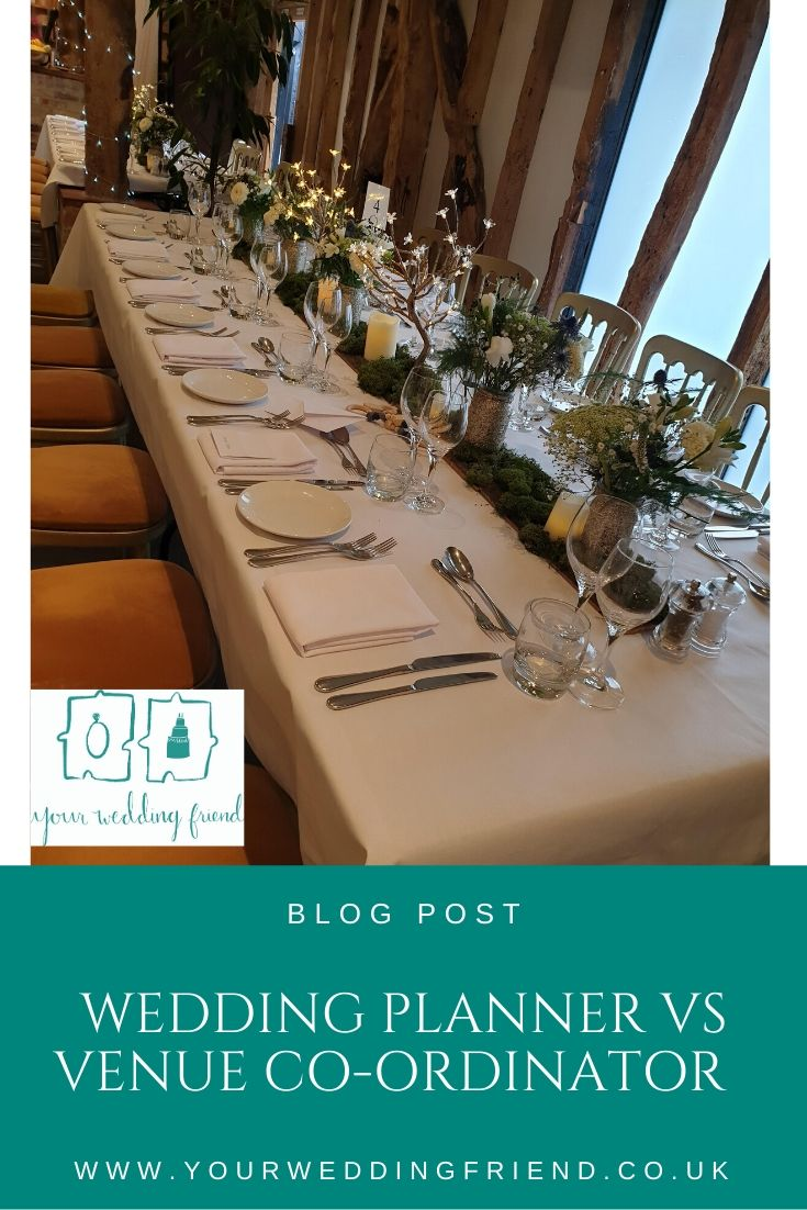 The image is of a long rectangular wooden table with a rustic centrepiece made of flowers in jars and bark and moss all along the middle length of the table